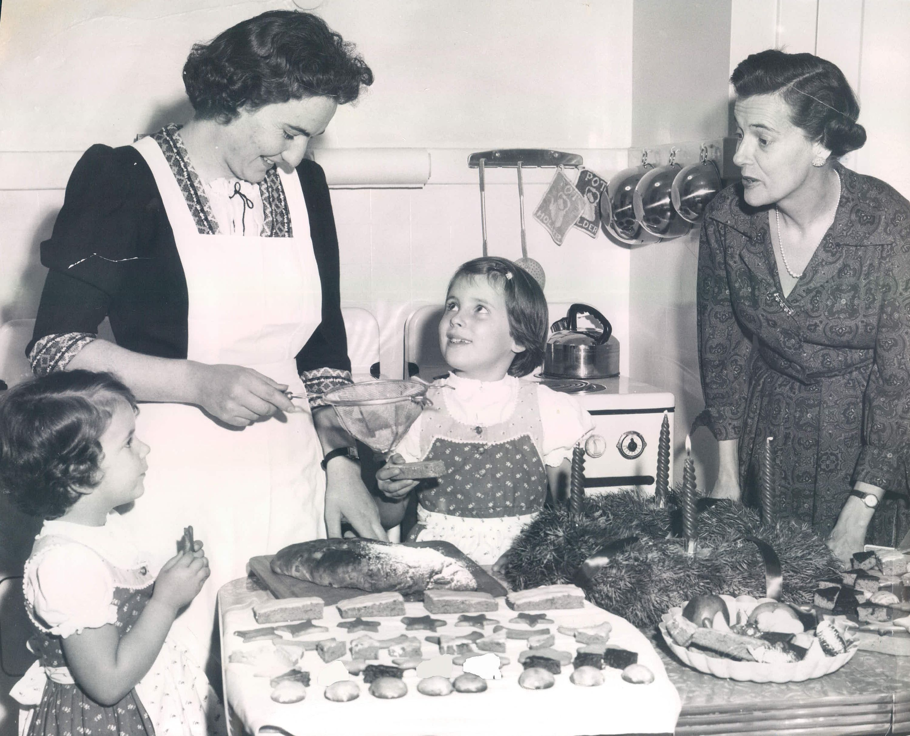 German Goodies: During Advent the German home is filled with the wonderful scent of the Christmas cookies and breads baking in the kitchen. The main celebration is Christmas Eve, when each family member finds a decorated plate full of the goodies under the tree. Keeping the custom here is Mrs. Otto Soltmann, right, wife of the German consul, who supervised the work of her German cook, Miss Edith Mallmann. Tasting goodies were the Soltmann daughters, Madeleine, left, 4, and Diana, 7. Today they will light the third candle on the Advent wreath for the third Sunday of Advent. (Photo by Harold Smith/The Seattle Times/JR Partners via Getty Images)