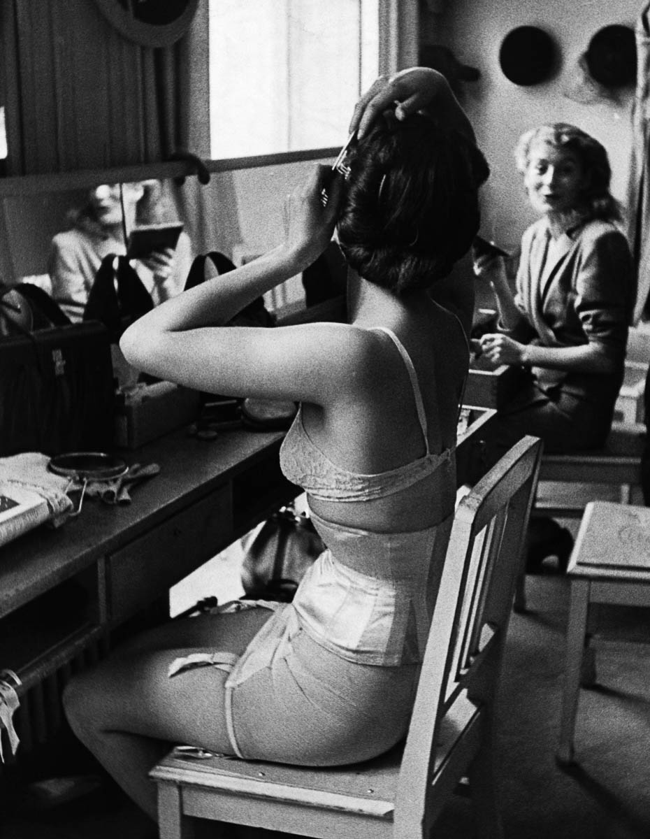 A fashion model curls her hair while she chats backstage at a show in the Piguet Fashion House. Paris, 1946. (Zdroj: © Hulton-Deutsch Collection/CORBIS/Corbis via Getty Images)